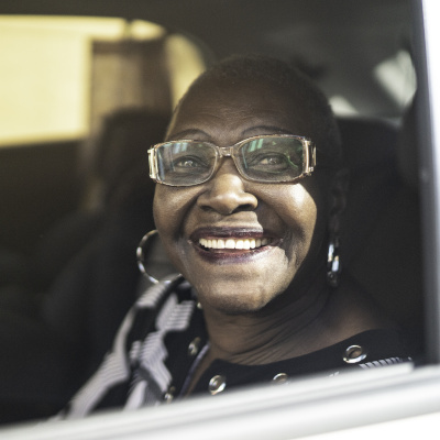 Older woman looking out car window while smiling