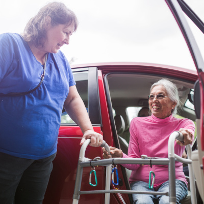 Woman helping another woman exit a car with a walker