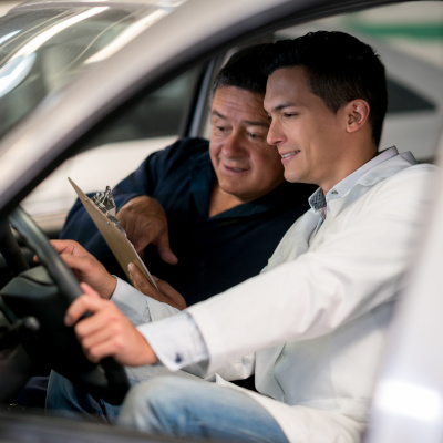 Two men in front seat of car going over paperwork on clipboard